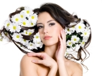 Beautiful sexy woman with  flowers in her long hair - white background